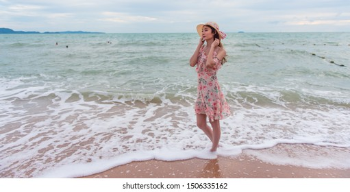 Asian traveller woman with hat walking on the beach background on summer beach vacation holiday concept.