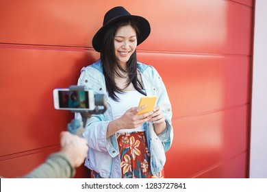 Asian trendy woman vlogging while using smartphone outdoor - Happy chinese girl having fun with new trends technology - Fashion, social network, tech and millennial generation activity - Focus on face