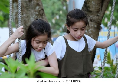 Asian twin girl are looking  something  in the garden.
