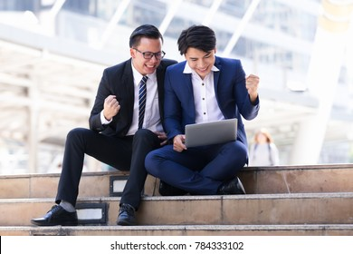 Asian two businessmen sitting are working on laptop in city