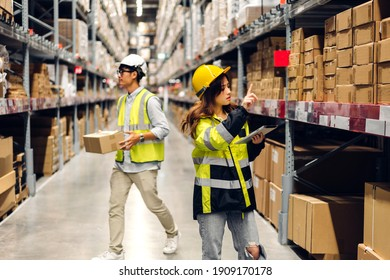 Asian two engineer in helmets team order details on tablet computer for checking goods and supplies on shelves with goods background in warehouse.logistic and business export