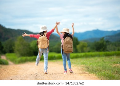 Asian two girl raise arms and jumping on the nature road, outdoors adventure and tourism for destination leisure trips with mountain for education and relax in jungle park. Travel vacations concept