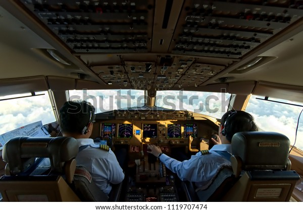 Asian two pilots were flying the commercial airplane. Seen from inside cockpit that can see cloud and sky through the window and all inside the cockpit. Real aviation concept.