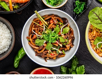 Asian udon noodles with spicy soy sauce and chicken pieces, top view, served on black stone.