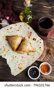 Asian Uzbek samsa dish with meat on pita bread with a glass of wine with spices on a wooden table