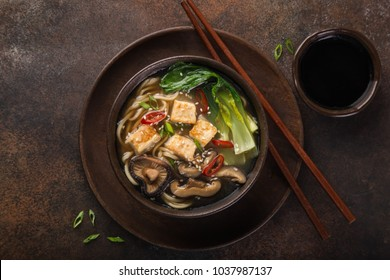 asian vegan noodle soup with tofu cheese, shiitake mushroms and pak choi, dark background, top view