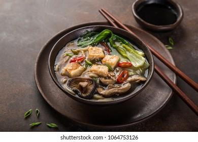 asian vegan noodle soup with tofu cheese, shiitake mushroms and pak choi, dark background, selective focus