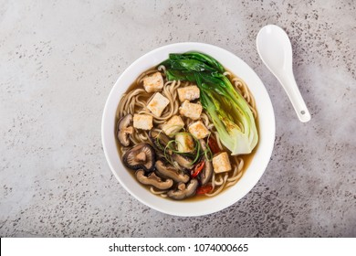 asian vegan noodle soup with tofu cheese,shiitake mushroms and pak choi in white bowl, top view, copy space