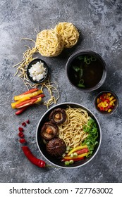 Asian vegan noodles with shiitake mushrooms, bell pepper and scallions served in a black bowl with vegetable. Top View
