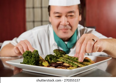 Asian vegetables. Close-up of fried asparagus, mushrooms and broccoli arranged in a plate by a cook in blurry