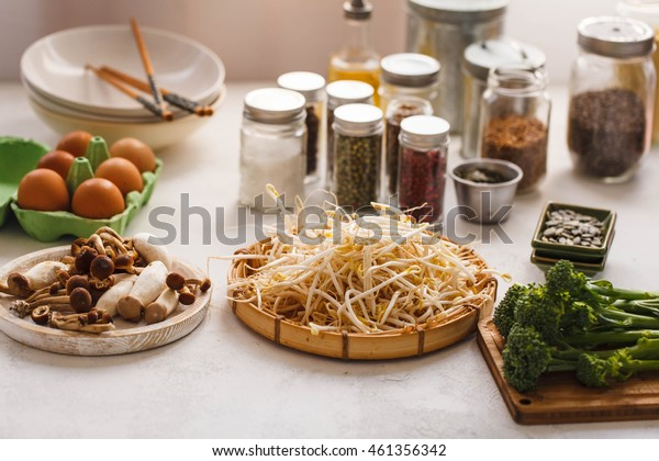 Asian vegetables. Mung bean sprouts, tenderstem broccoli and shiitake mushrooms over kitchen table with variety condiments glass jars.