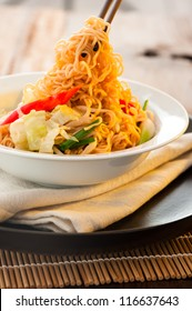 Asian vegetables noodles in white plate and chopsticks on wooden table as background