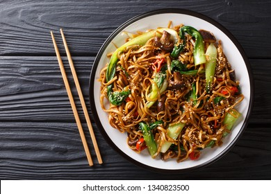 Asian vegetarian food udon noodles with baby bok choy, shiitake mushrooms, sesame and pepper close-up on a plate on the table. horizontal top view from above
