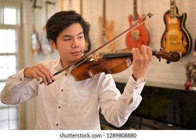 Asian Violinist playing the violin at the home. Musician playing at home.