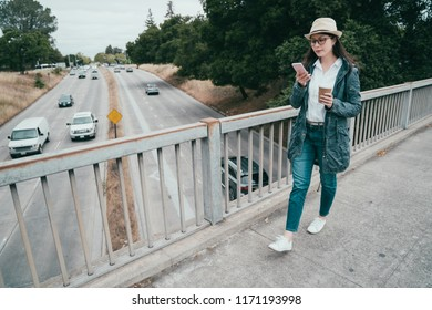asian visitor using smartphone and holding a cup of coffee while walkin on the bridge.