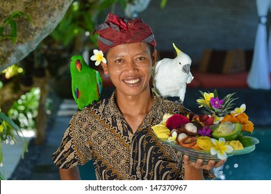 Asian waiter with a tray of tropical fruits in an exotic setting. Shoot in a luxury resort on Bali island, Indonesia