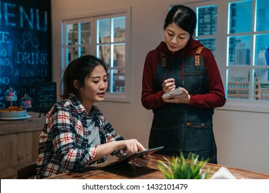 asian waitress takes order in restaurant using note and pen writing standing talking with client in night pub in modern city. cute girl customer point on digital tablet screen choose meal in bar.