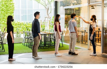 Asian waitress wear protective face mask scan customer temperature by thermometer before entering the restaurant to protect infection from coronavirus covid-19, social distancing concept