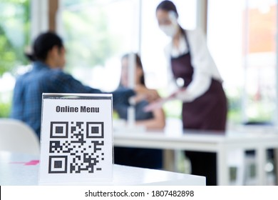 Asian waitress woman show qr code online menu for customer select meal in restaurant.New normal lifestyle sevice.