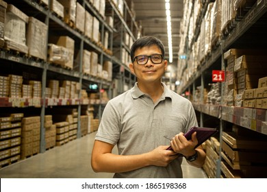 Asian warehouse manager holding tablet for check stock.Thai people working in storehouse.