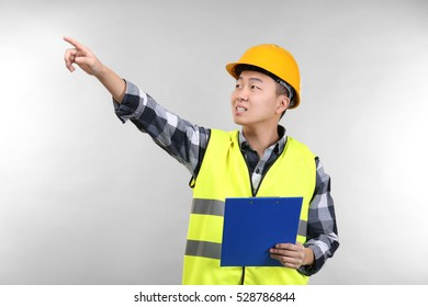 Asian warehouse worker with clipboard pointing at something, on light background