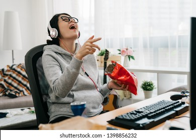 asian weird computer geek stay at home on summer vacation. high school girl laughing watching online series comedy movie on pc cheerful eating junk food snack chips cookies unhealthy lifestyle.