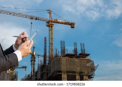 An Asian white engineer wore a suit and a safety hat on his head and watched the building construction plan by working on radio communications.