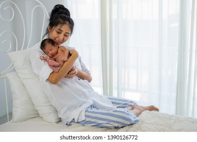 Asian white shirt mother holds her little sleeping newborn baby on her chest and sit on white bed in front of glass windows with white curtain.