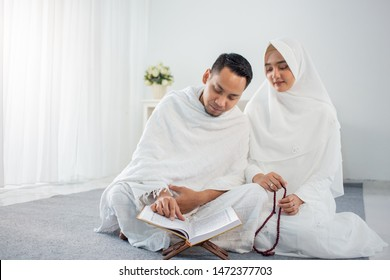asian wife and husband praying with Al-Qur'an and tasbih in white traditional clothes
