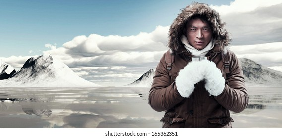 Asian winter sport fashion man with backpack in snow mountain landscape. Wearing brown jacket with fur hoody and white gloves.