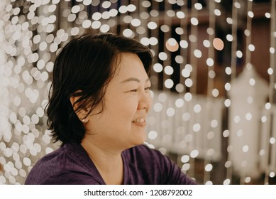 Asian woman 40s plump body fashion happy for relax in night time with bokeh of light decoration for happy new year celebration