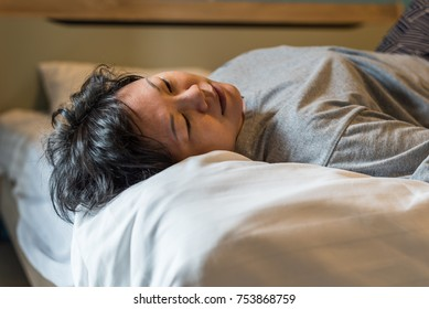 Asian woman 40s plump body take a nap or sleep on a white bed in bedroom for rest and relax because fatigue or tired