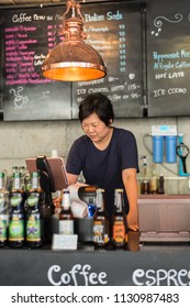 Asian woman 40s white skin plump body is coffee shop owner work as a cashier service to customers in the coffee shop cafe