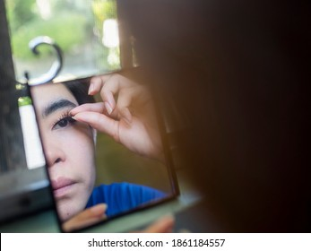An Asian woman adjusts her fake eyelashes with her hand while looking at a small mirror placed by a window sill. Shot at the bedroom.