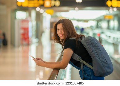 Asian woman in airport. Casual professional businessman using smartphone with backpack, smiling happy at airport.
