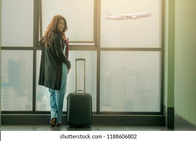 Asian woman in the airport, looking through the window at planes.