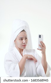 Asian woman apply hydrogel face mask, young woman wrap towel on head skin care routine concept playing smart phone mobile on white background