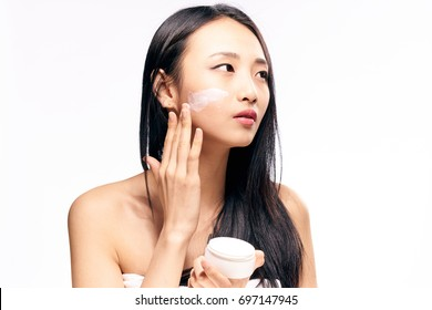 Asian woman applying cosmetic cream on facial skin care face on isolated background