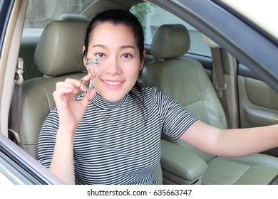 Asian woman applying makeup while driving her car