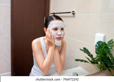 Asian woman applying mask on her face and looking in the mirror in the bathroom