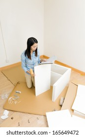 Asian woman assembling closet with instruction