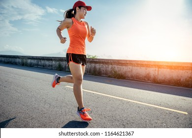 An asian woman athletic is jogging on the concrete road, she is warming her body and tideten her tying her shoes tightly fitting before workout.