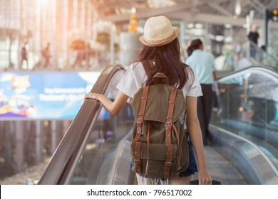 Asian woman with backpack in airport terminal on escalator traveler at international airport, young girl tourist lifestyle on holidays