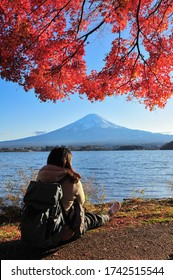 Asian woman backpacker sits and hugs her knees up to the chest under the red maple tree beside lake Kawaguchiko with Fuji mountain background during sunset in autumn