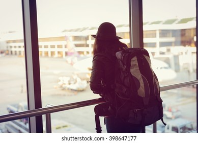 Asian woman backpacker solo travels and waiting for the flight at the airport terminal. Young female traveling outdoor by backpack.