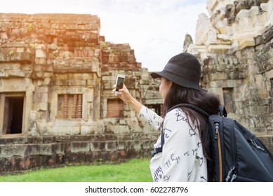 Asian woman backpacker solo travels and take a photo with smartphone outdoor lifestyle at ancient in Thailand