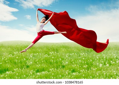Asian woman ballerina holding red fabric making a big jump on blossom meadow. Summer or Spring concept