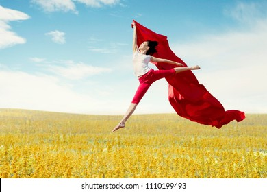 Asian woman ballerina holding red fabric making a big jump on meadow. Summer or Spring concept