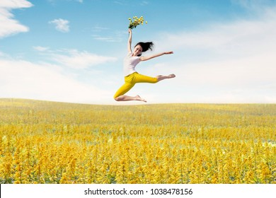 Asian woman ballerina holds bouquet of flowers making a big jump on meadow. Summer or Spring concept