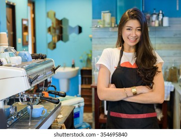 Asian woman barista coffee standing and smiling with crossed arms  beside coffee machine in counter - young attractive female successful in small business owner woking woman